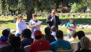 Tony Anderson Executive Director Valley Mountain Regional Center speaking to the audience with a microphone at Parkview Cemetery in Modesto.